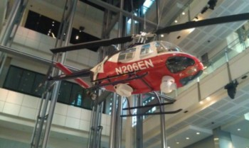 A suspended news helicopter hangs overhead
