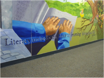 A powerful mural, painted by middle school students, lines the hallways